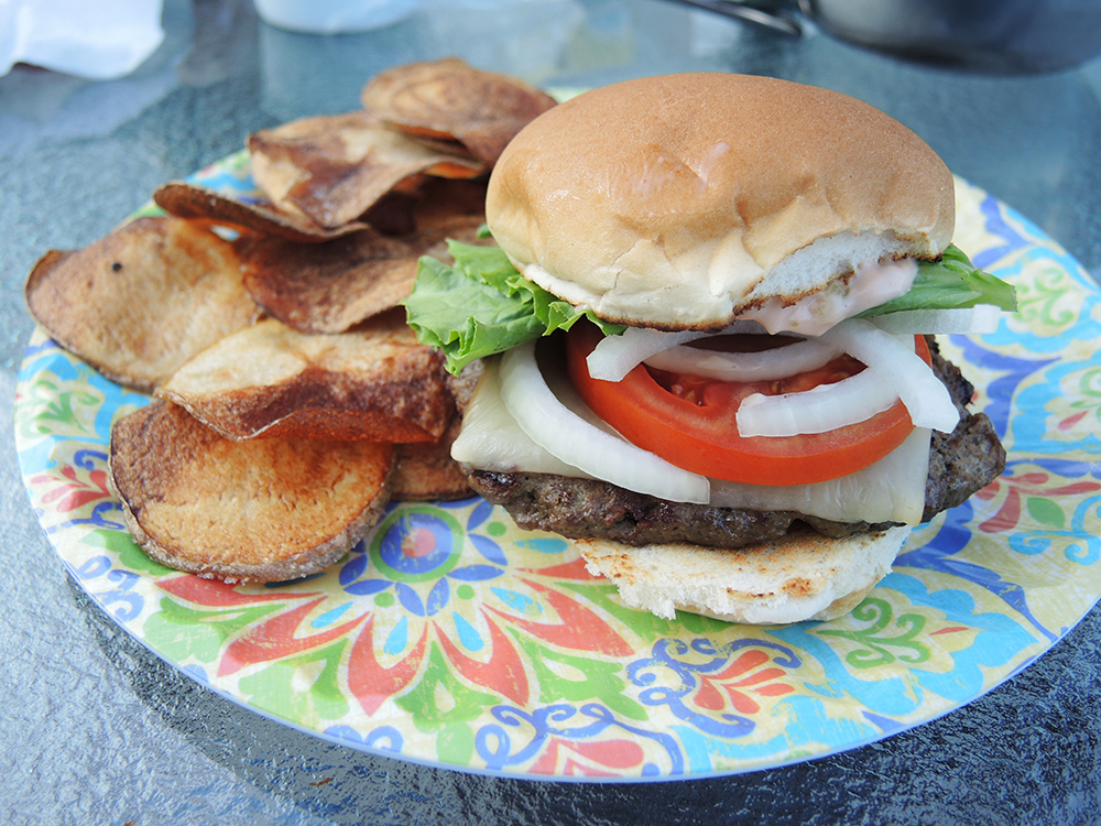 hamburger and perfect party food The perfect hamburger with cheese, bacon,  cookout american bbq food big hamburger with steak meat and vegetables closeup with chef unfocused at background.